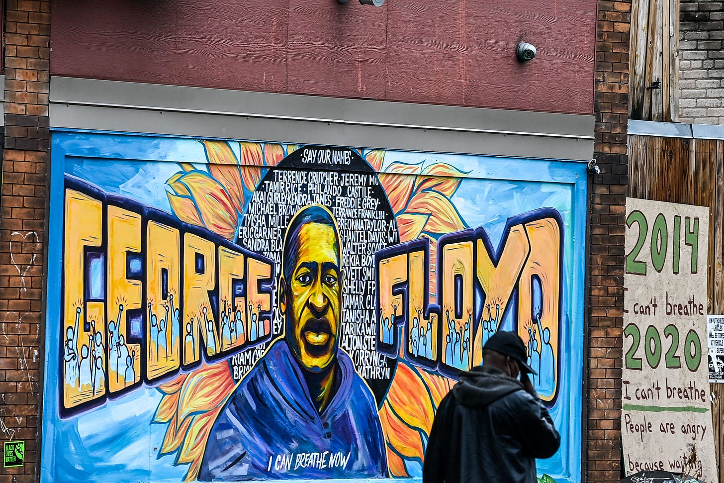 """A man walks past the mural of George Floyd near the makeshift memorial of George Floyd before the third day of jury selection begins in the trial of former Minneapolis Police officer Derek Chauvin who is accused of killing Floyd, in Minneapolis, Minnesota on March 10, 2021. - The first jurors were selected on March 9, 2021 in the high-profile trial of the white police officer accused of killing George Floyd, an African-American man whose death laid bare racial wounds in the United States and sparked """"Black Lives Matter"""" protests across the globe. Former Minneapolis Police Department officer Derek Chauvin is facing charges of second-degree murder and manslaughter in connection with Floyd's May 25 death, which was captured by bystanders on smartphone video. (Photo by CHANDAN KHANNA / AFP) (Photo by CHANDAN KHANNA/AFP via Getty Images)"""