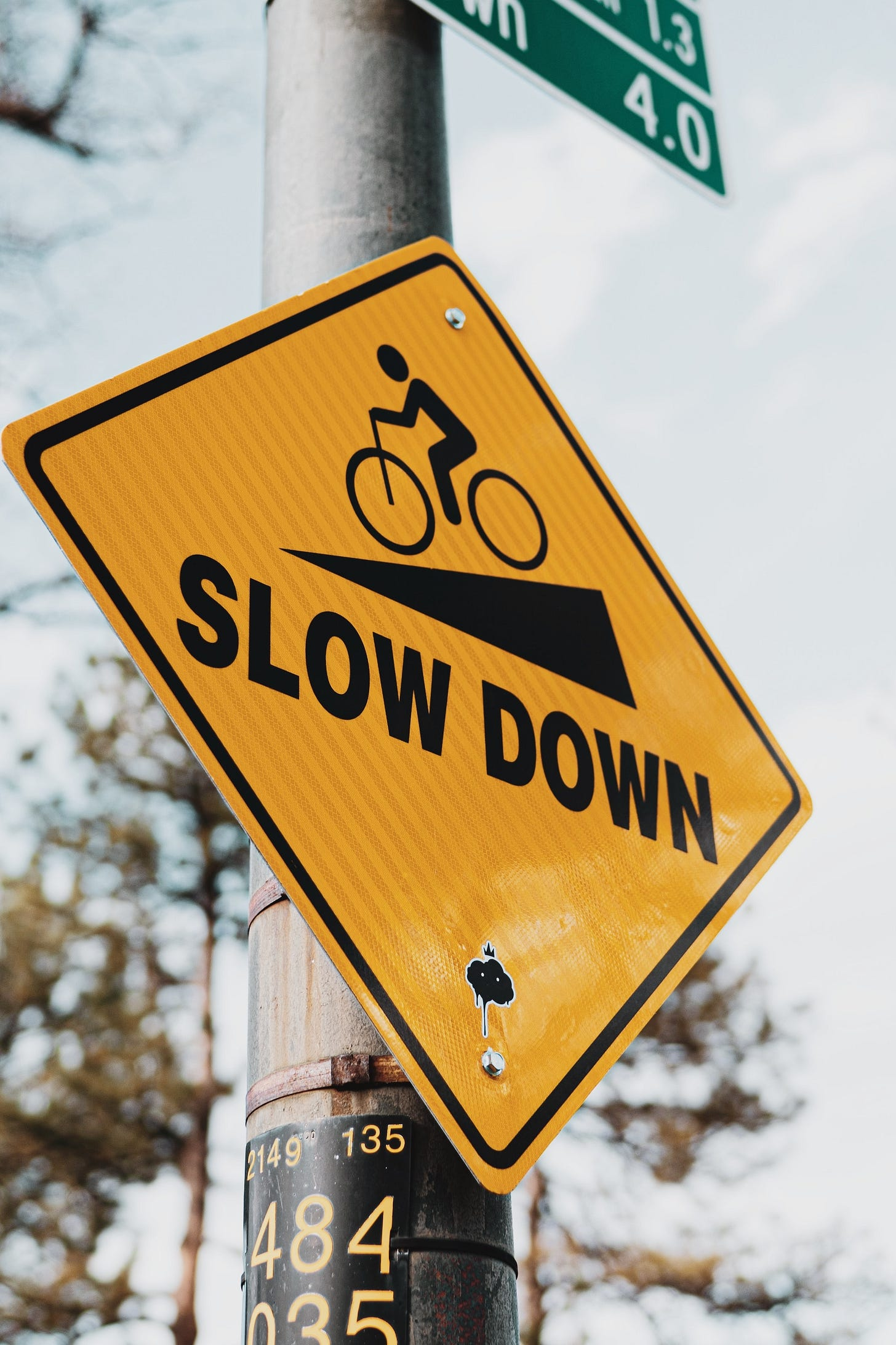 """Traffic sign saying """"slow down"""" with image of cyclist"""