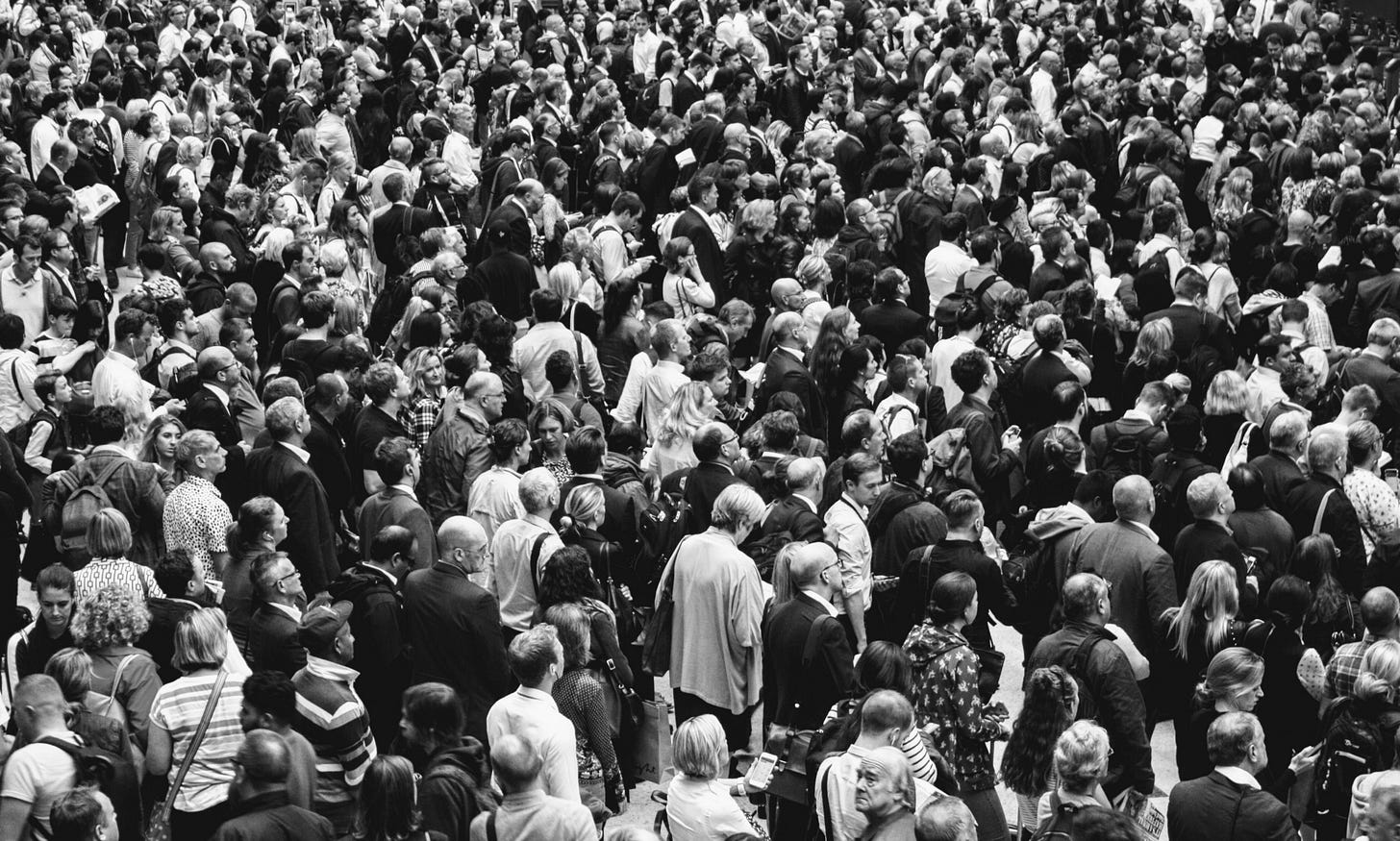 black and white image of a crowd for article by Larry G. Maguire