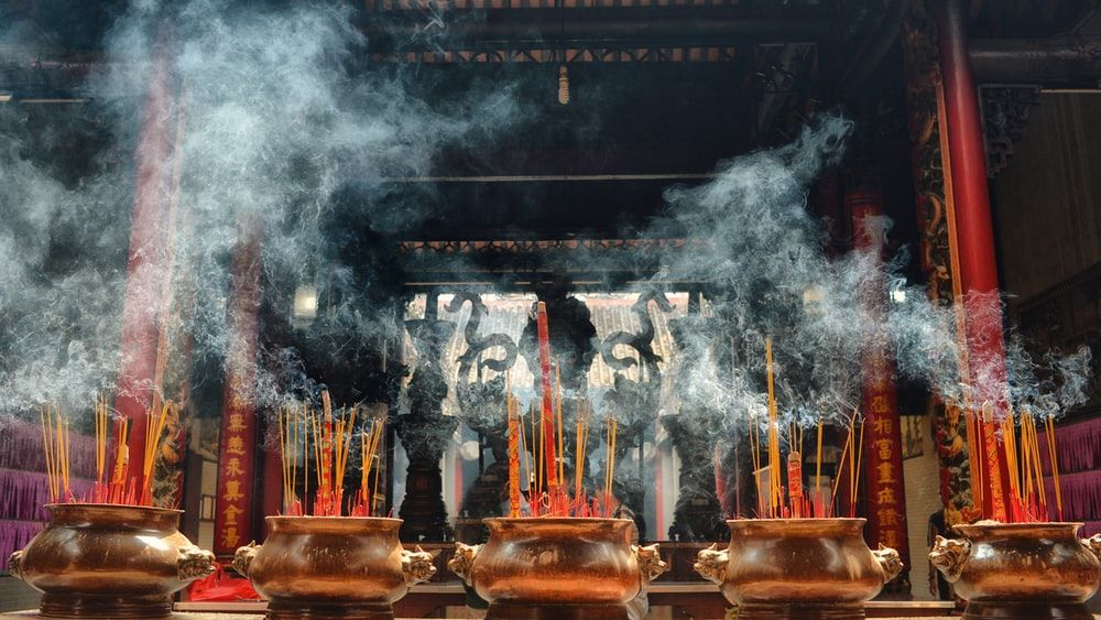 A photograph of a temple in Hanoi, with burning incense on brown vases