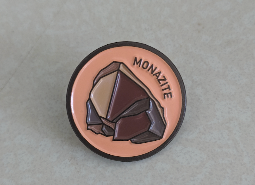 """An enamel pin with an illustration of a reddish-brown rock against a salmon-ish background. The word """"monazite"""" curves around the right side of the rock."""