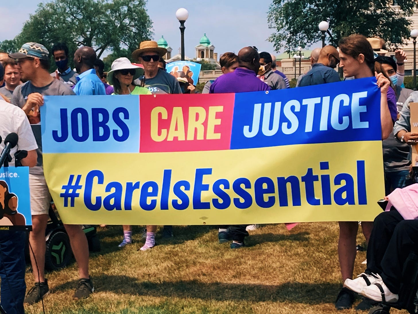 """people hold up banner with text reading """"jobs care justice #careisessential"""" in blue and yellow text with yellow, red, and blue background"""