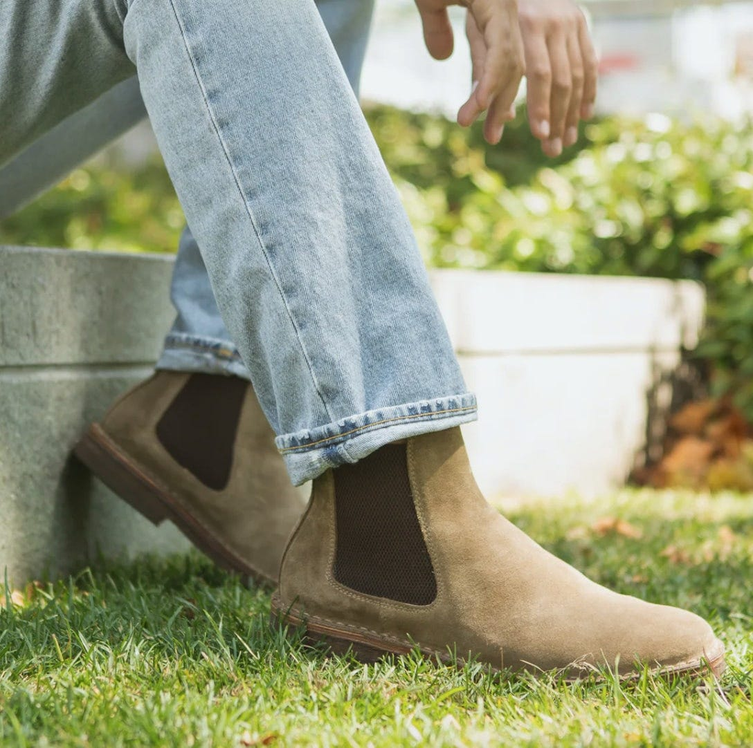 a man wearing light colored jeans with natural suede chelsea boots