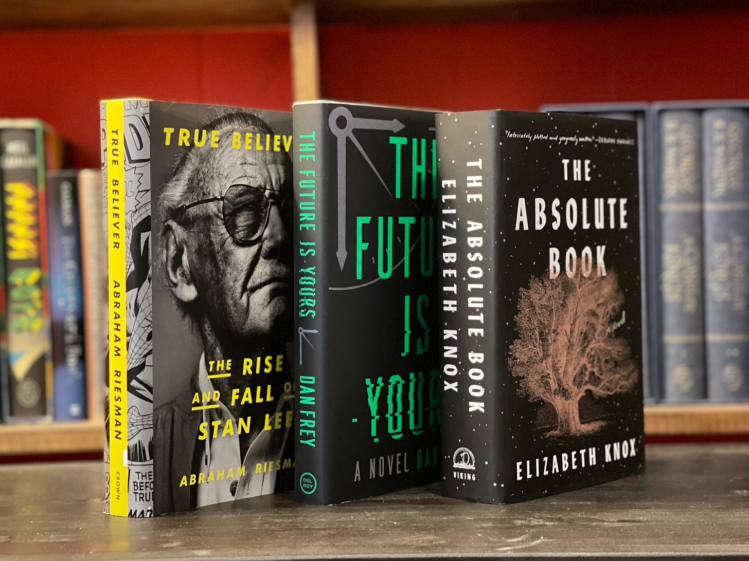 Three books stand up on a table: True Believer, The Future is Yours, and The Absolute Book