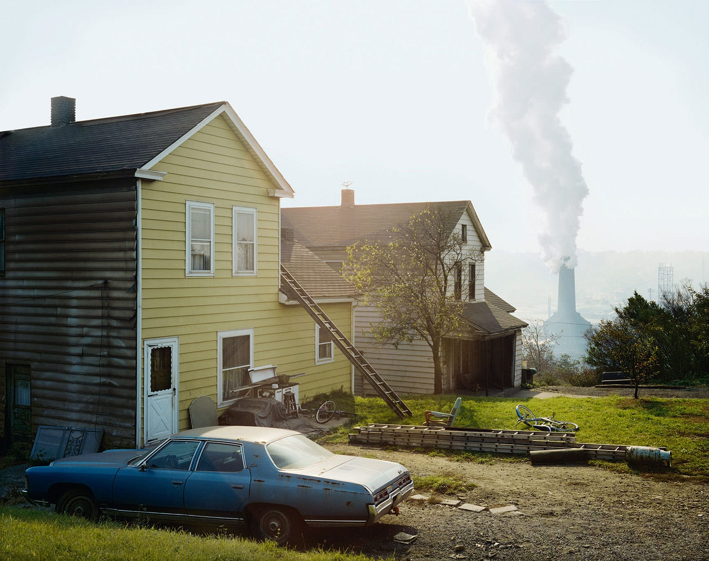 Two run-down houses on a hill with smokestack of steel mill just beyond