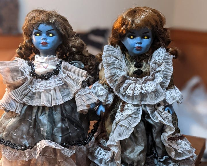 Two creepy dolls with blue faces and glowing yellow eyes.