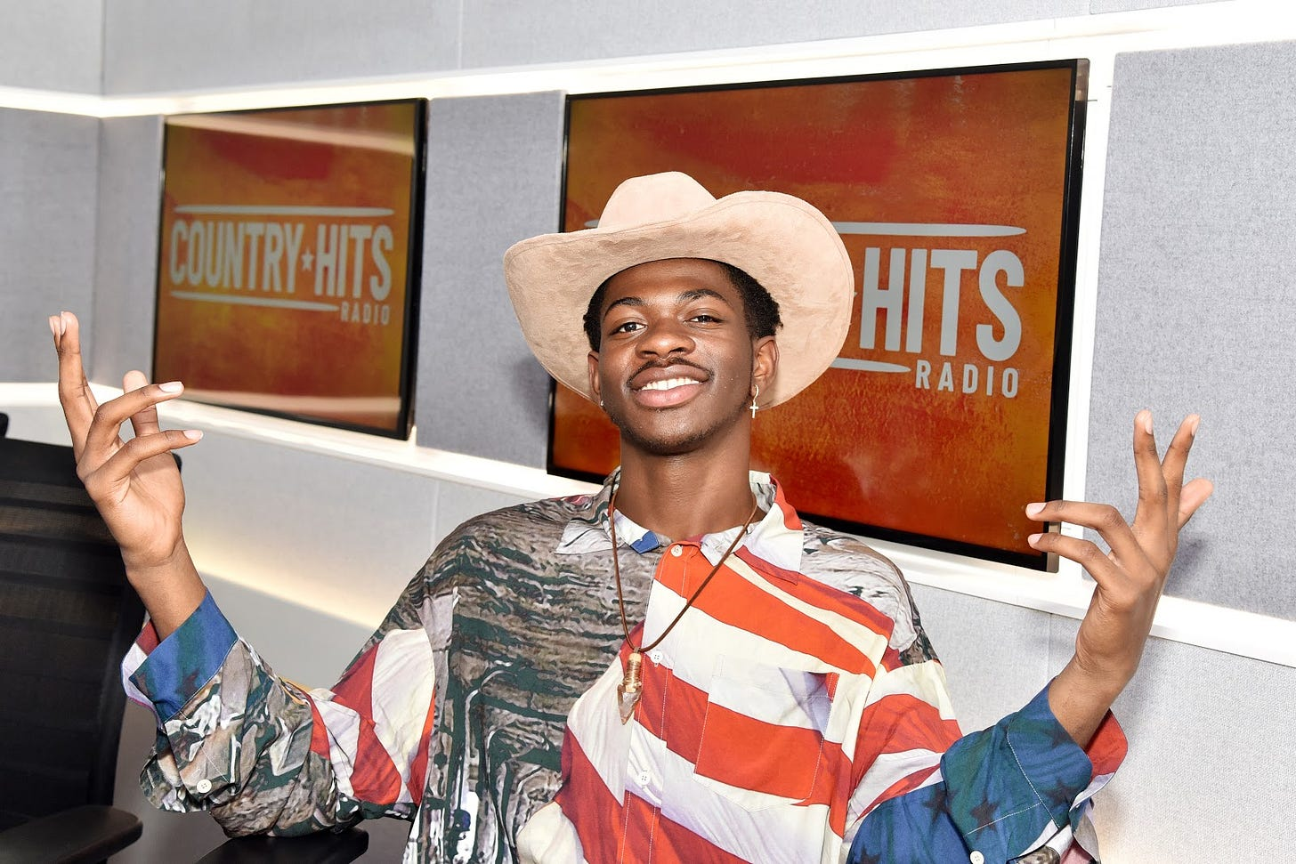 """Photo of Lil Nas X wearing an American flag button down and cowboy hat, sitting in front of two televisions that display a """"Country Hits Radio"""" emblem."""