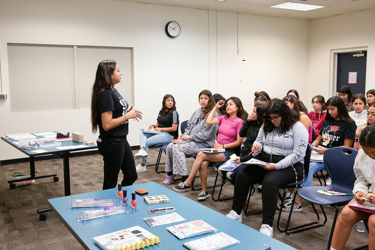A teacher stands before a classroom full of students, with a table holding nail polish and other prizes in the background.