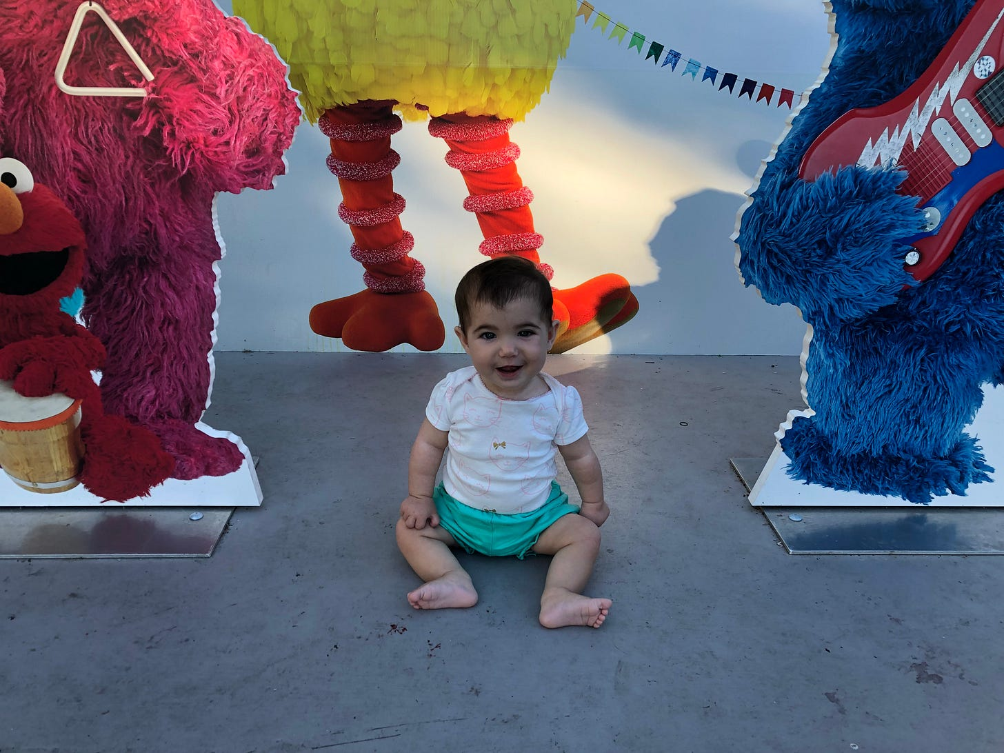 Small baby with a giant smile sits upright between cutout figurines of sesame street characters.
