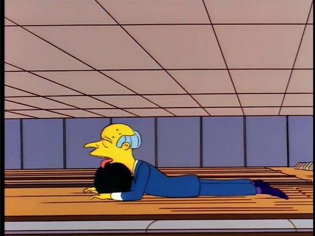 A screenshot from The Simpsons, showing Mr. Burns lying on the bowling alley floor, his tongue lolling out over a bowling ball, after he fails to throw it more than a foot.