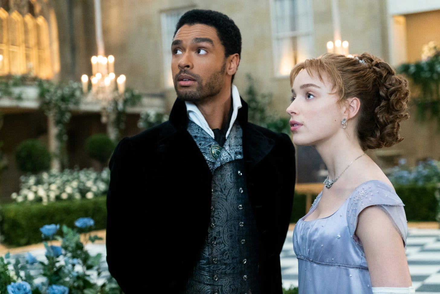 Simon and Daphne in Bridgerton, standing together and looking off-screen to the left