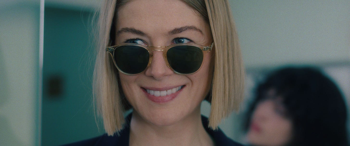 Shot of Rosamund Pike as Marla in I CARE A LOT looking over the top of her sunglasses and smiling
