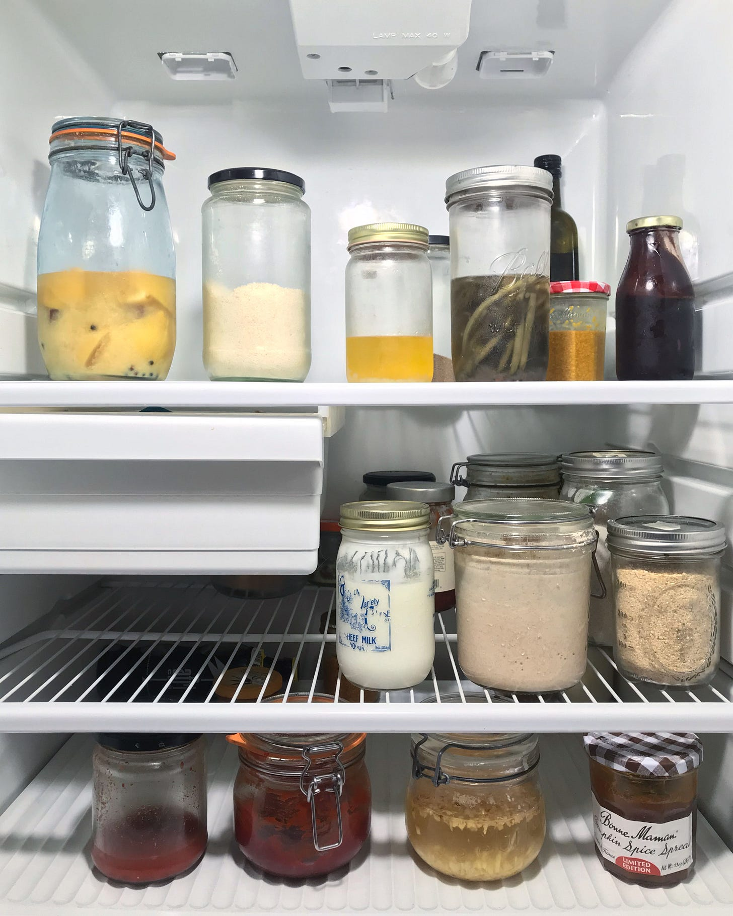3 shelves in a refrigerator, filled with clear glass jars of various kinds of food