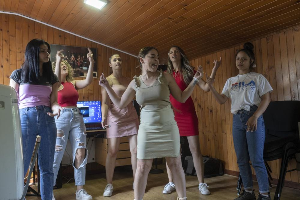 """Zlata Ristic, 27, center, Elma Dalipi, 14, left, Silvia Sinani, 24, 2nd left, Dijana Ferhatovic, 18, 3rd left, Zivka Ferhatovic, 20, 2nd right, and Selma Dalipi, 14, members of the Pretty Loud band, practice at a music studio in Belgrade, Serbia, Wednesday, June 16, 2021. A female Roma, or Gypsy, band in Serbia has used music to preach women's empowerment within their community. Formed in 2014, """"Pretty Loud"""" symbolically seeks to give a louder voice to Roma girls, encourage education and steer them away from the widespread custom of early marriage. (AP Photo/Marko Drobnjakovic)"""