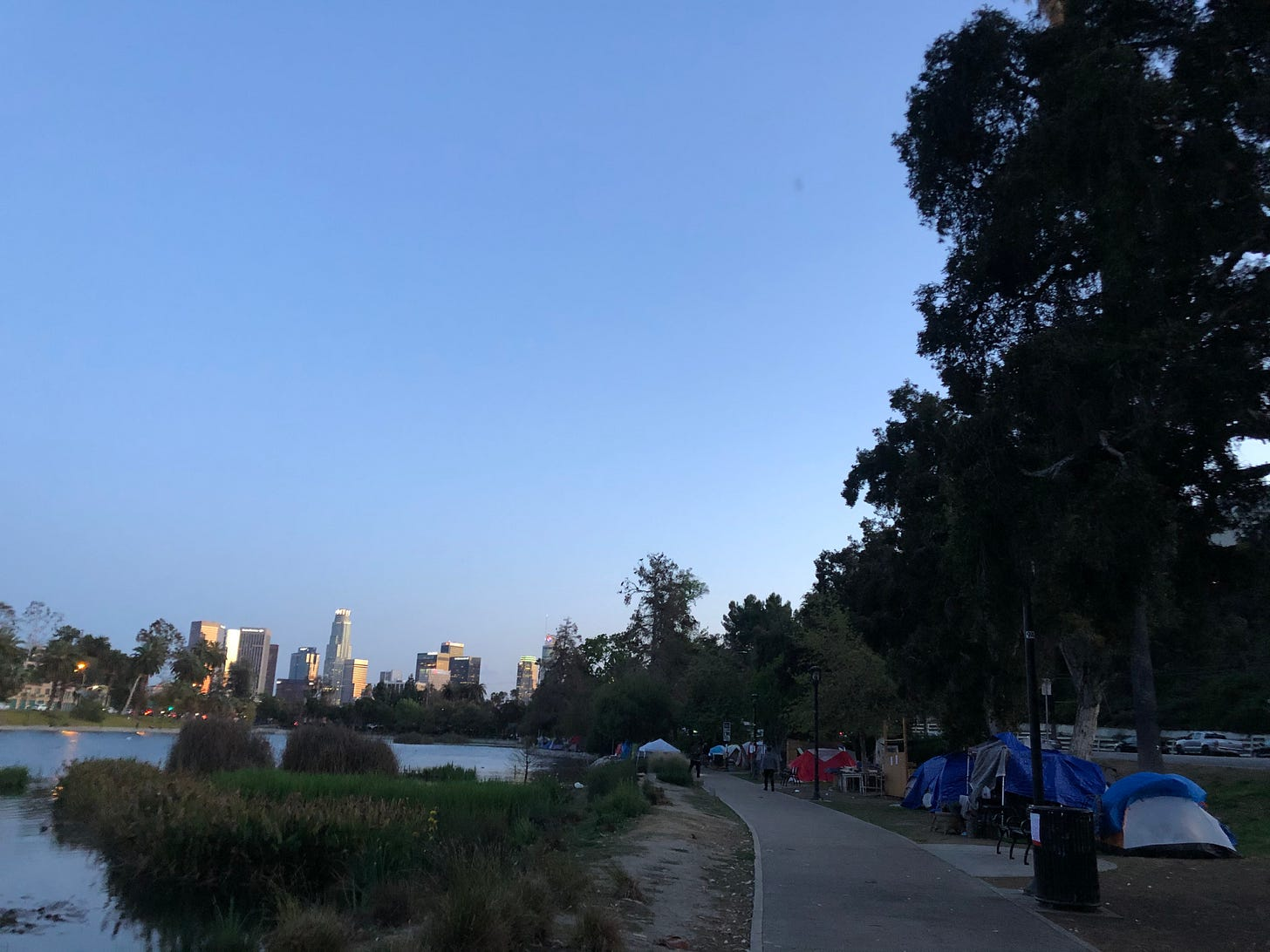 A view of a park lake in the foreground, skyscrapers in the background, and a line of tent shelters on the right.