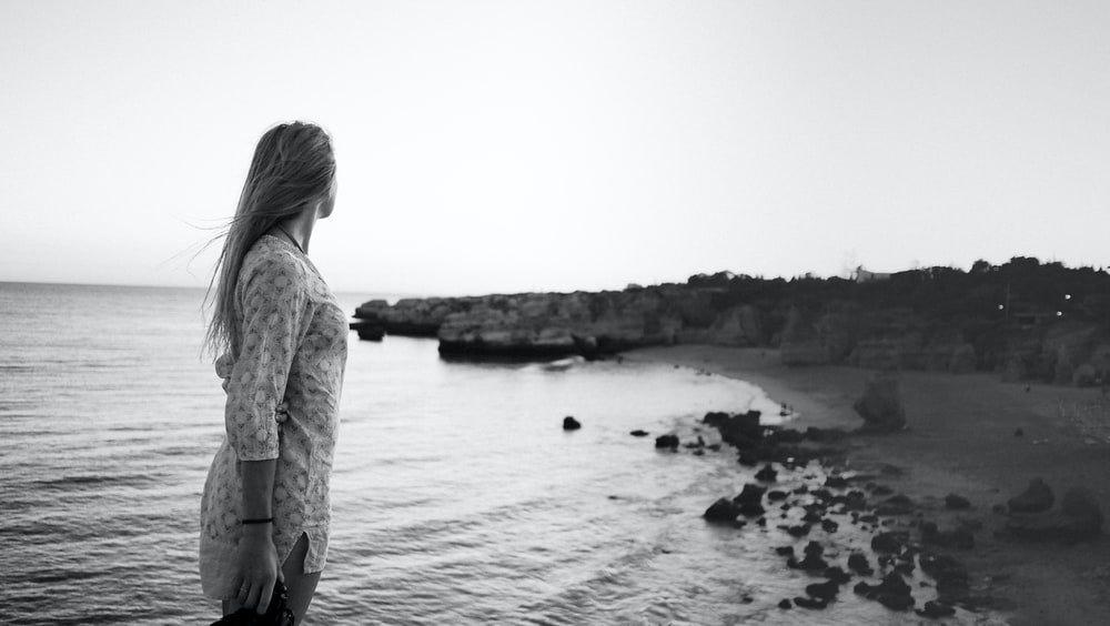 woman standing on seashore grayscale photography