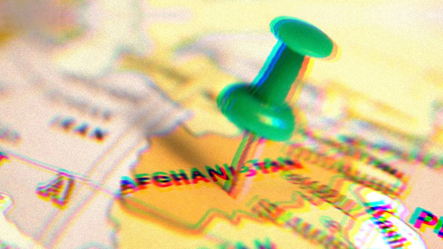 Green pushpin pressed into a map, the pin is sticking into Afghanistan