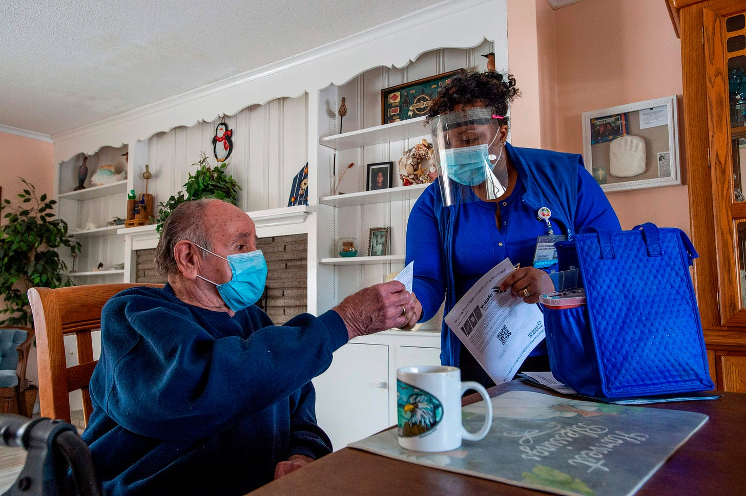 R.N Natalie O'Connor hands a vaccine card to Stanley Mowel (L) before vaccinating him at his home in Manchester, Connecticut on February 12, 2021