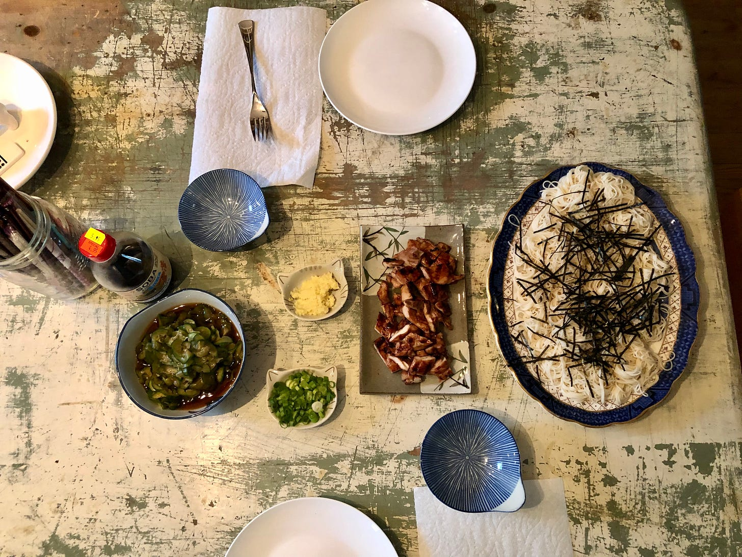 Overhead shot of a table with dishes of cold somen noodles, grilled chicken, and vinegared cucumber slices. There's also a bottle of store-bought dipping sauce for the noodles.