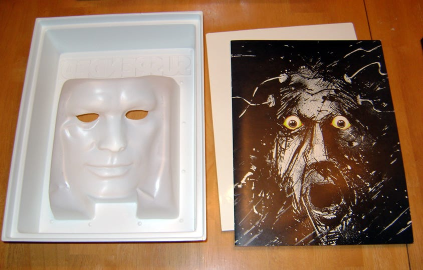 Inside of the original Suspended mask box, showing the plastic mask and the sketch of a screaming man inside.