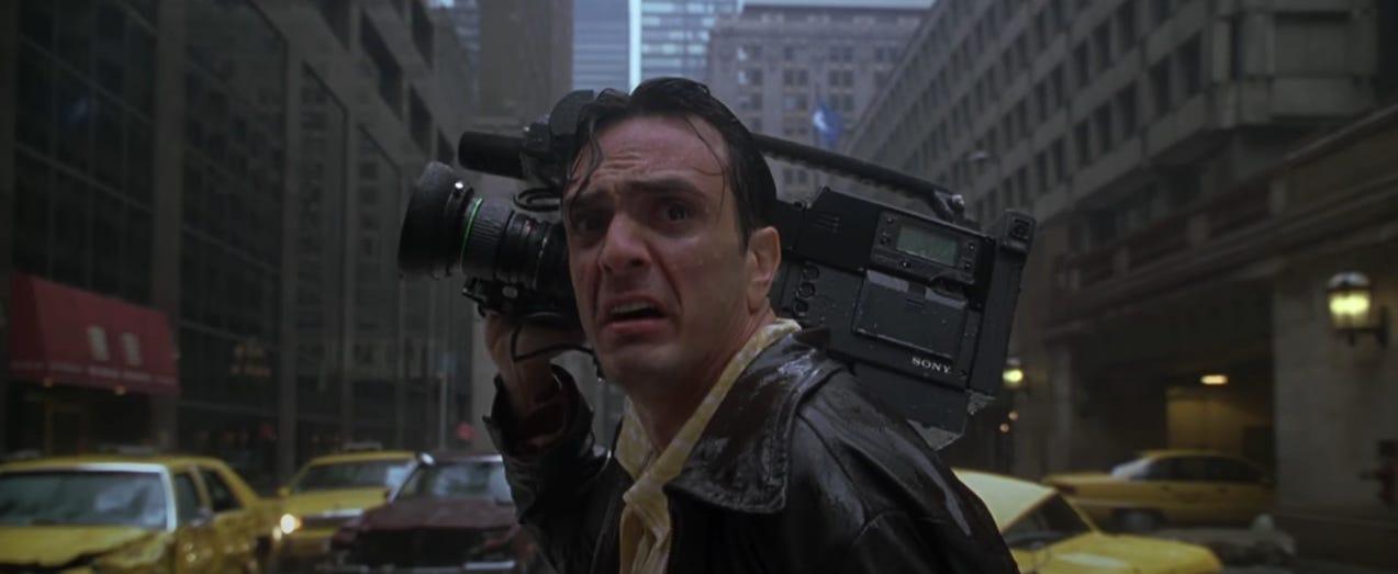 Hank Azaria's news cameraman character, looking back in shock at the giant legend Godzilla, in New York street rain. From the 1998 film 'Godzilla'