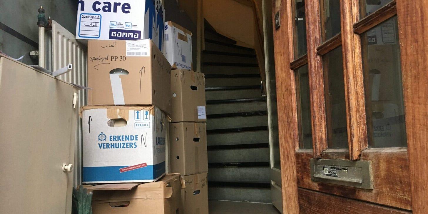 foto van een open voordeur met daarachter een trapgat en heel veel verhuisdozen