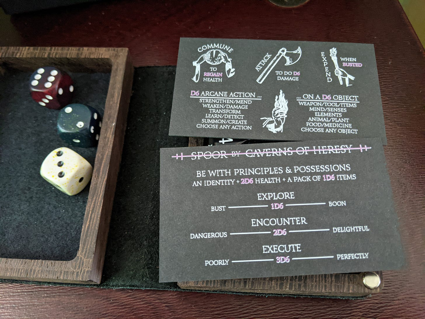 A picture of a dice tray and the front and back of Spoor - a business card rpg