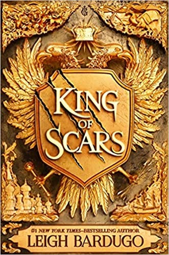 The book cover for King of Scars by Leigh Bardugo. The cover is covered in gilded gold designs and a double headed golden eagle whose wings are spread wide and hold a shield with the title scrawled across it.