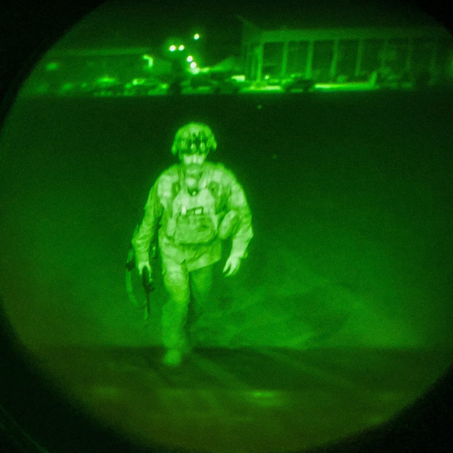 A man in full combat uniform boards a plane at night.