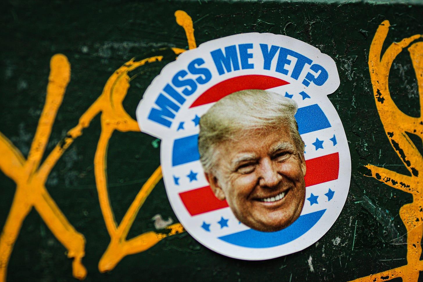"Trump's face on a sticker with the words ""Miss me yet?"" Jon Tyson / Unsplash"