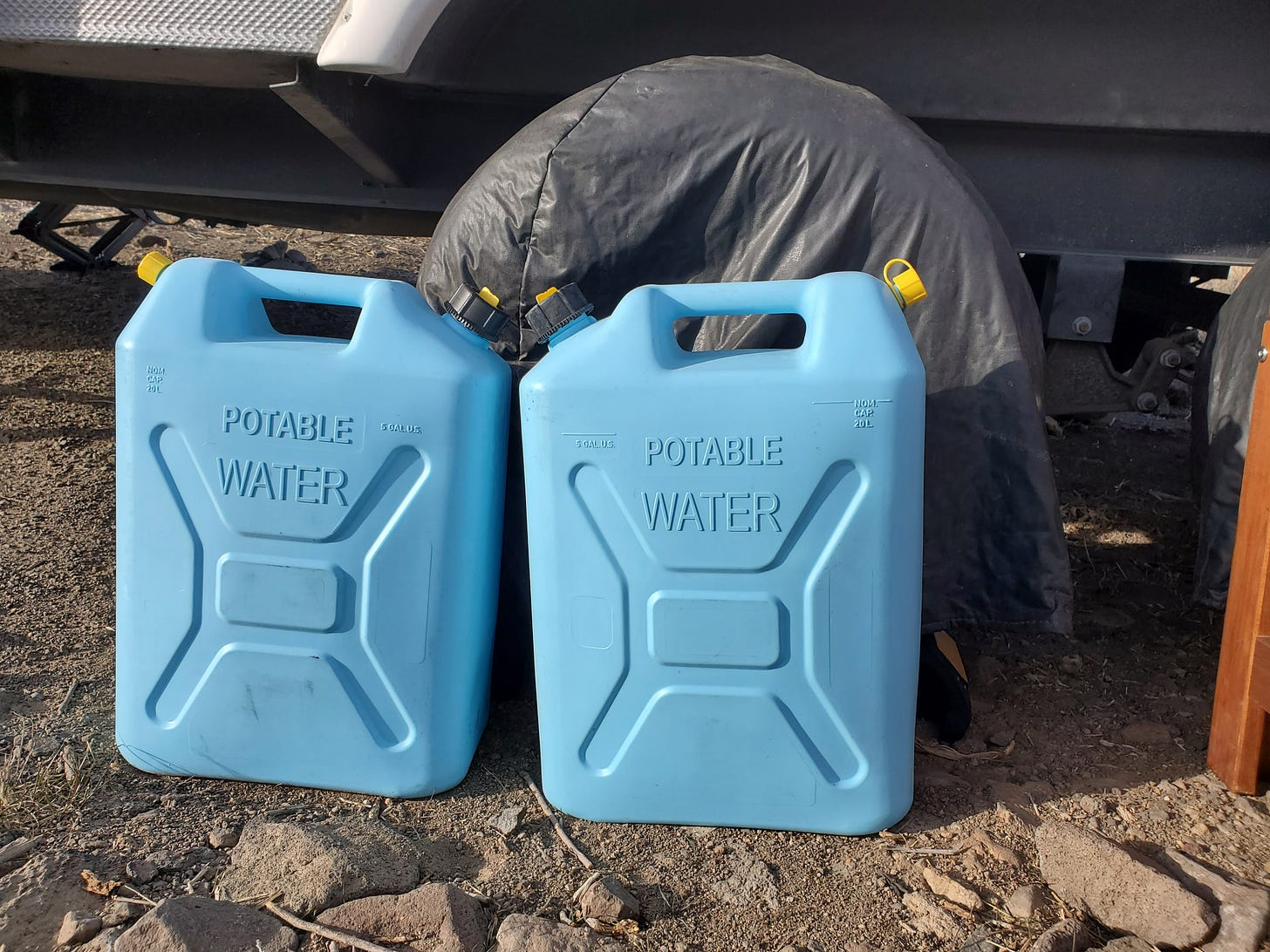 Two blue plastic containers that say Potable Water on the ground in front of a wheel of the travel trailer.