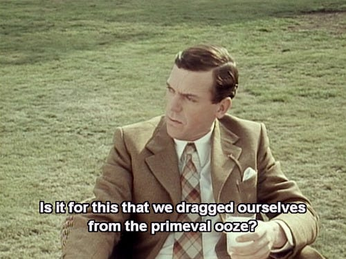 """still image from the TV show Jeeves & Wooster showing Hugh Laurie's character Bertie Wooster. He is seated and holding a drink, wearing a tan suit, saying """"Is it for this that we dragged ourselves from the primeval ooze?"""""""