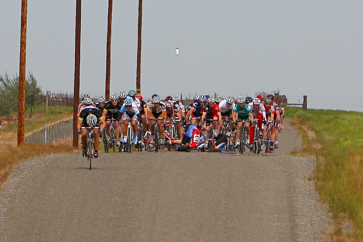 Photo of a bike race crash. A water bottle floats in the air.