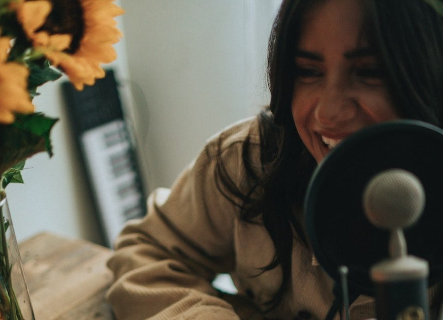 Woman speaking into podcast microphone