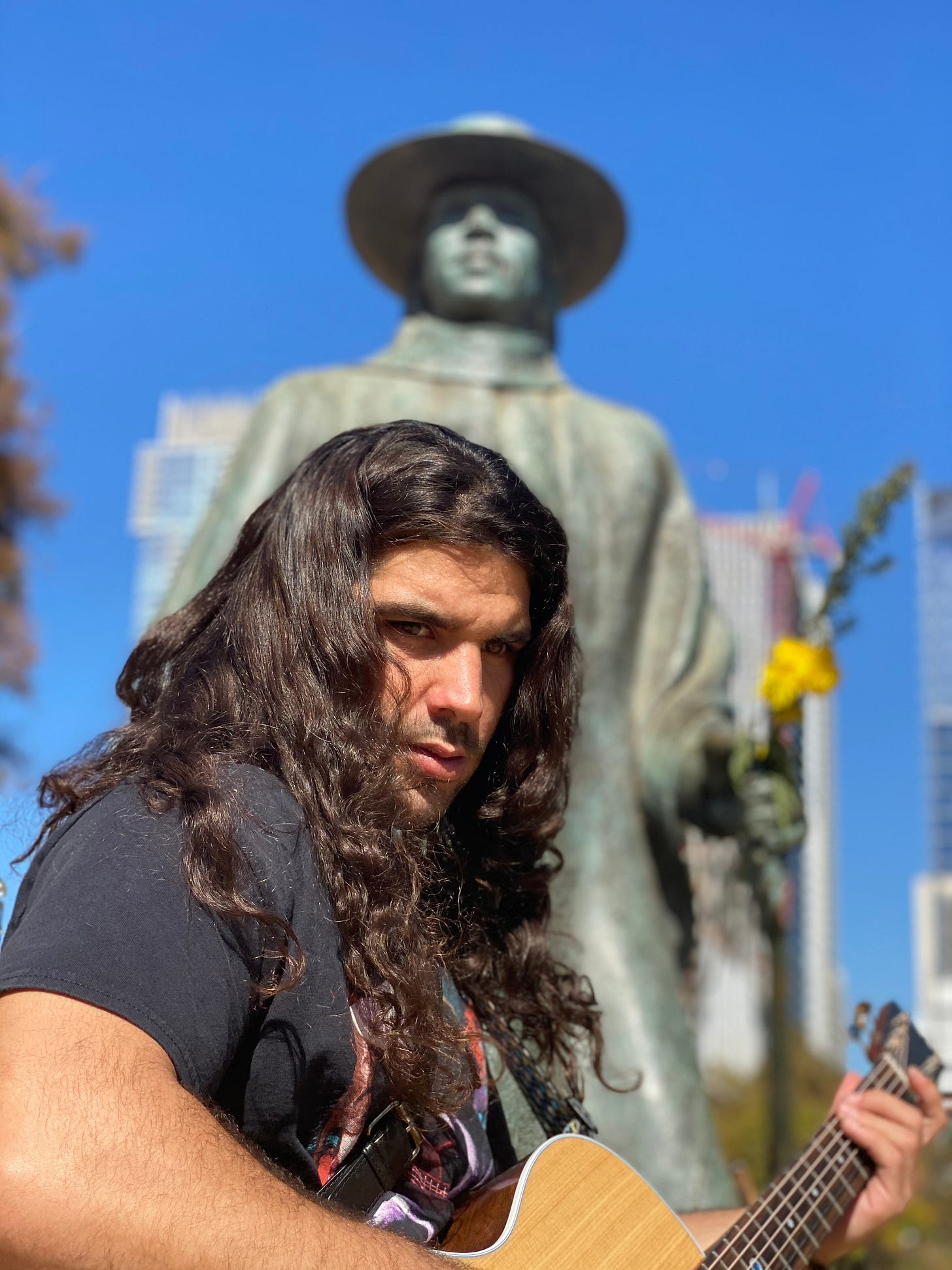 anthony standing so serious with his hear down and shining so beautifully and statue of stevie ray vaughn is behind his head blurred out
