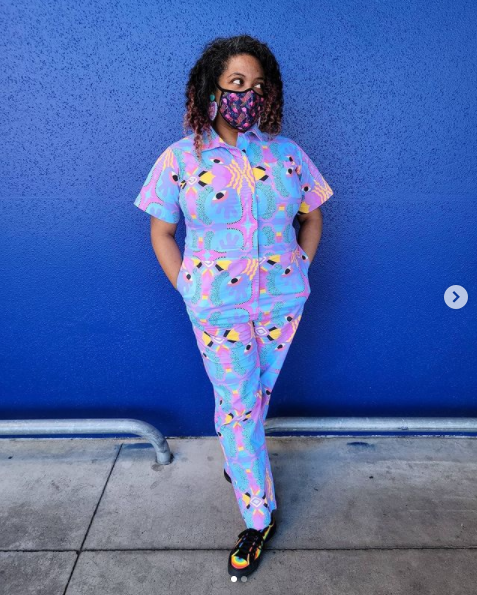 Photo of Patricia standing with her hands in her pockets in front of a bright blue wall. She is wearing a multicolored jumpsuit and a tropical print face mask. She is looking to the right.