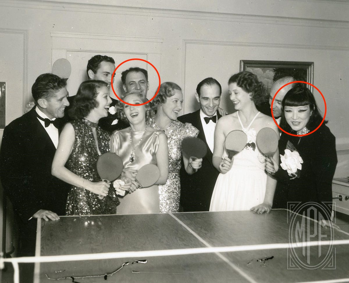 The Mary Pickford Foundation photo of Mary Pickford and a group of friends partying around the ping-pong table at Pickfair circa 1935; red circles identify Harry Lachman and Jue Quon Tai.