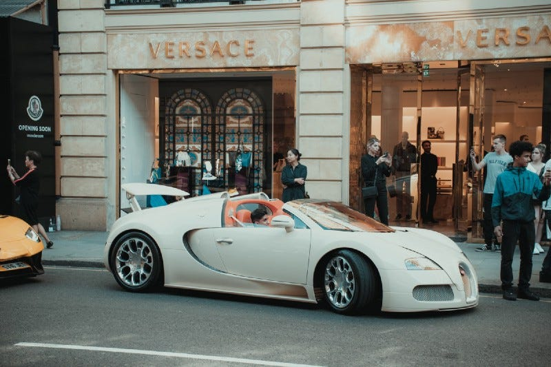 A young rich kid in a supercar in front of a Versace store