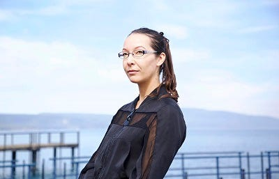 Picture of Essa Hansen. She has brown hair tied back and glasses and is looking diagonally past the camera. She is wearing a blue and brown jacket and standing outdoors, with a body of water and a blue sky visible in the background.