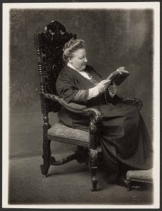 Photo of Amy Lowell seated in a chair reading a book.