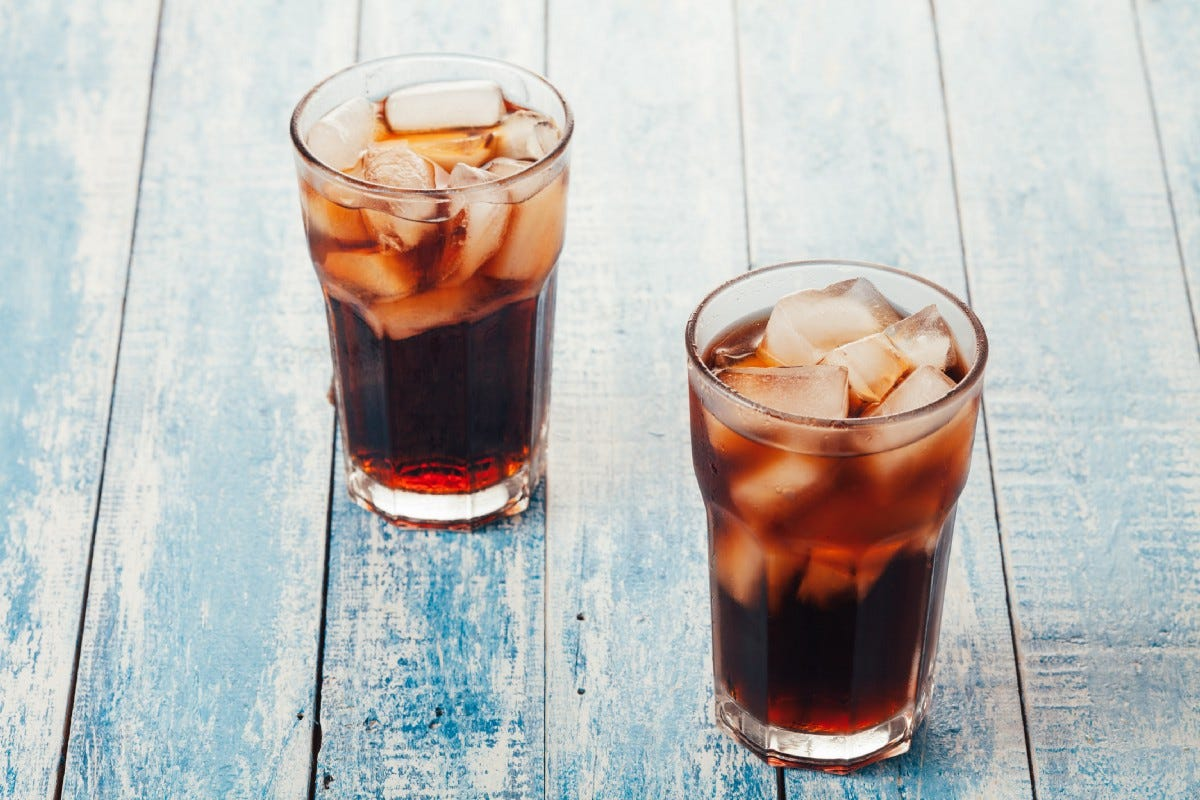 Two glasses, filled with dark opaque liquid and ice cubes, on thin weathered blue planks of wood.