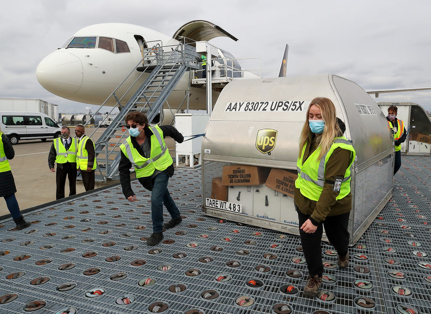 UPS employees move one of two shipping containers containing the first shipments of the Pfizer and BioNTech COVID-19 vaccine a ramp at UPS Worldport in Louisville, Kentucky, on December 13, 2020. The flight originated in Lansing, Michigan. (Photo by Michael Clevenger - Pool/Getty Images)
