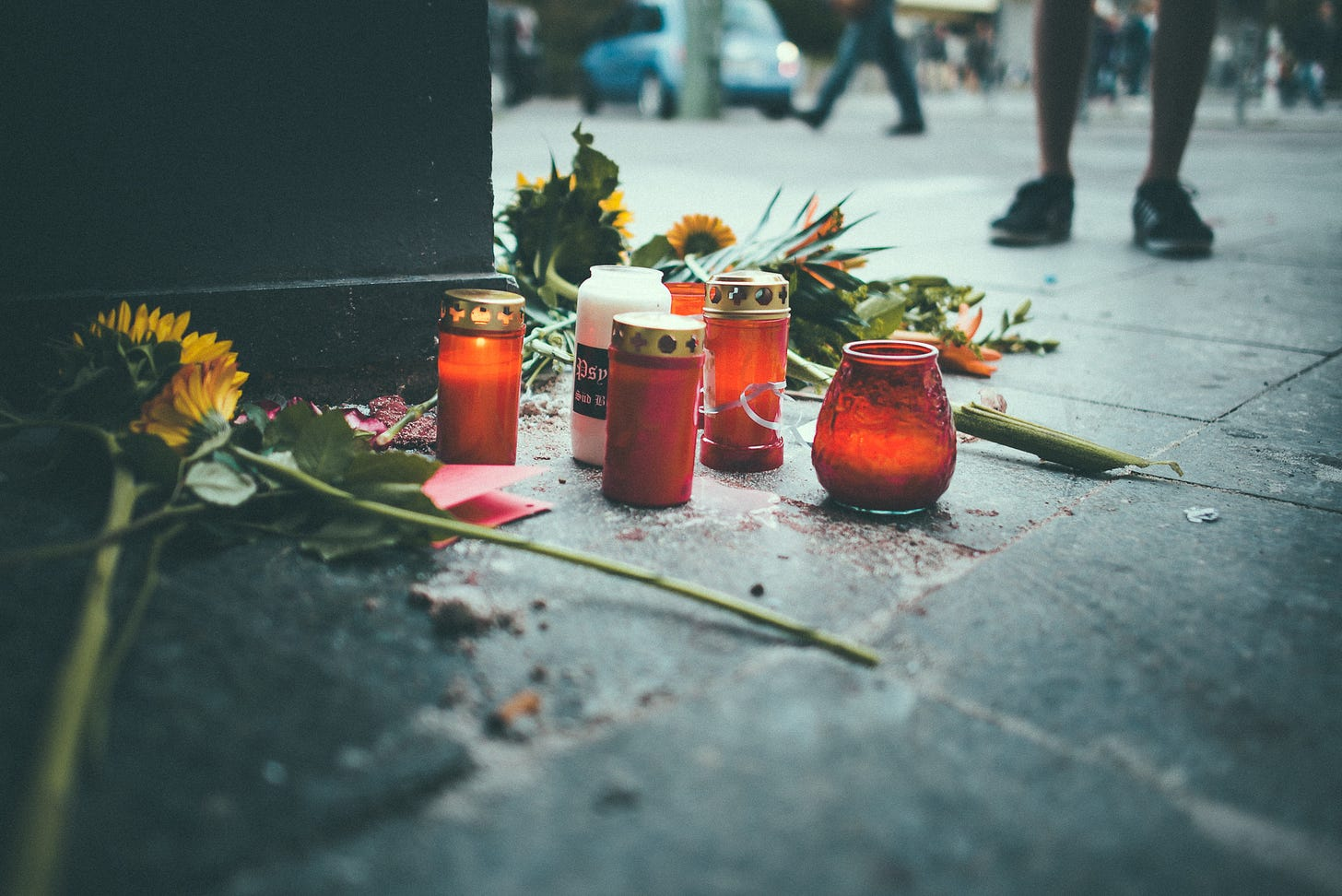 Candle and flowers on the ground in a public street as people walk by and one person stands by them