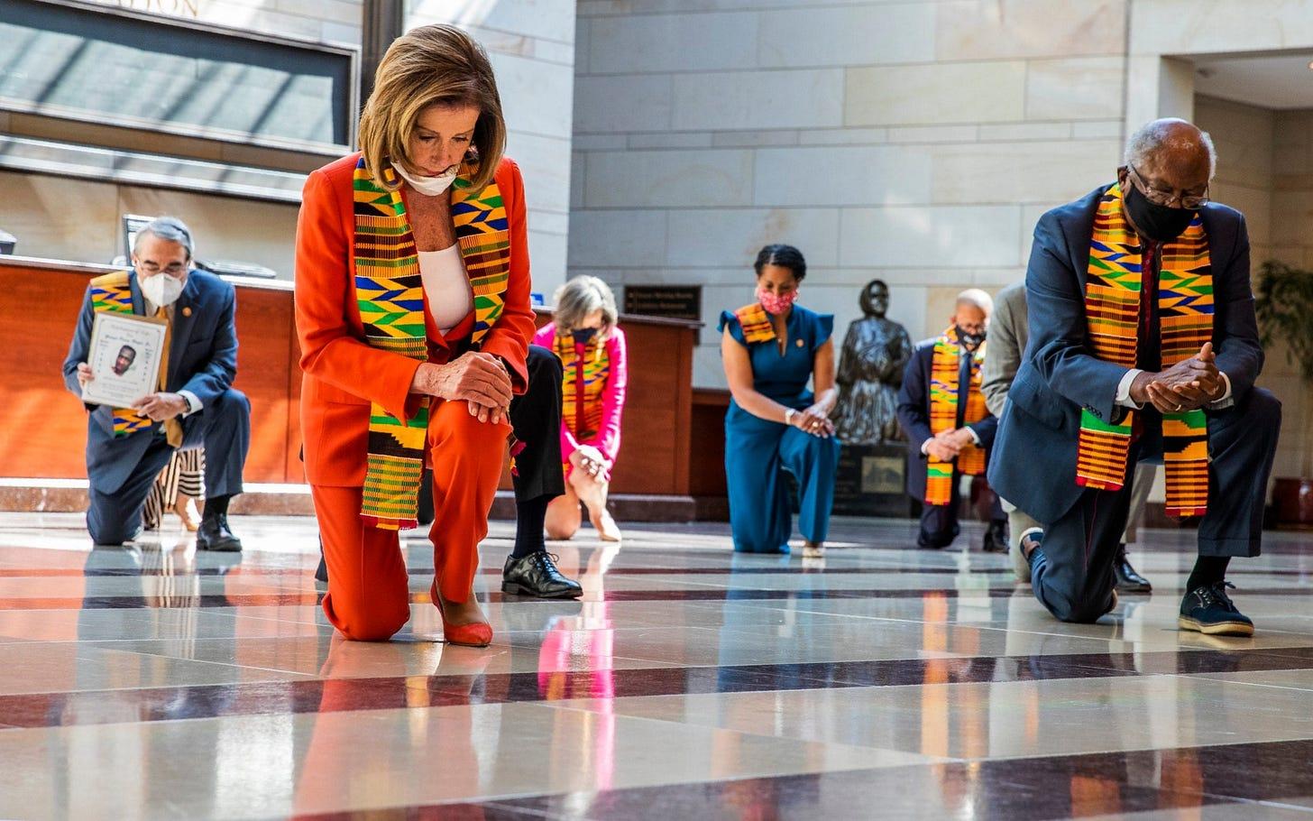 image of Nancy Pelosi and members of congress wearing kente cloth scarves and kneeling
