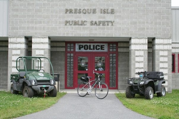 """A golf cart, a bicycle and an all-terrain vehicle are parked in a row in front of a building. The building is gray concrete with four columns and a bright red entrance with double doors. Above the doors, are signs reading """"Presque Isle Public Safety"""" and """"POLICE""""."""