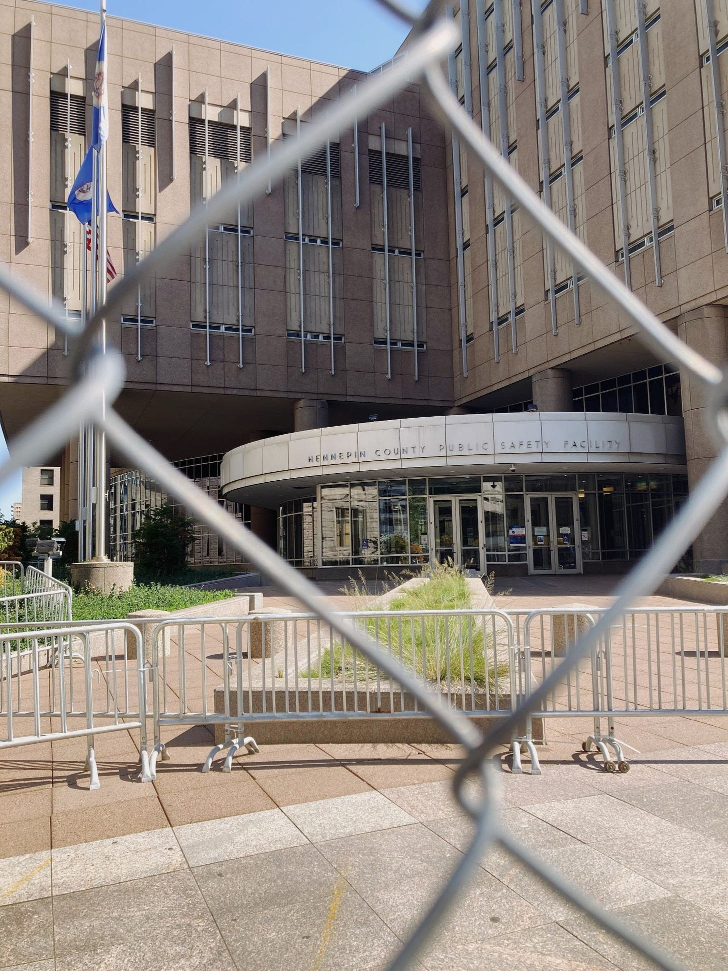 The entrance to the Hennepin County Public Safety facility, a beige brutalist building with skinny windows and metal bars