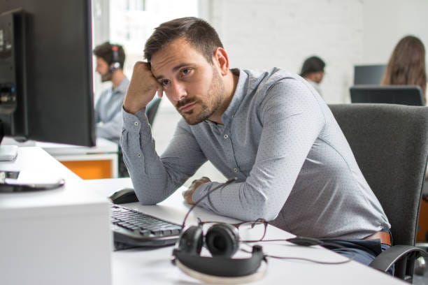 Worried beard man looking at computer screen in office Worried beard man looking at computer screen in office depressing job stock pictures, royalty-free photos & images