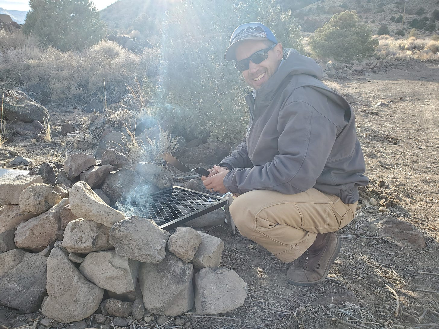 Eric squatting in front of a DIY grill supported by rows of rocks.