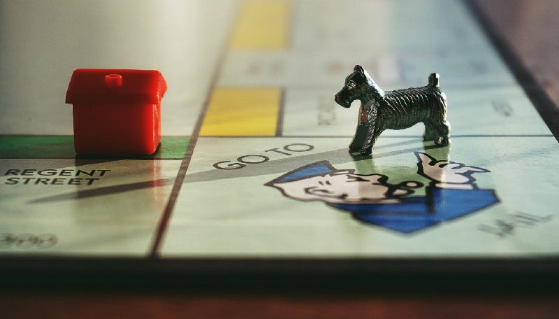 A Monopoly board game, with a pewter dog facing a red plastic house.