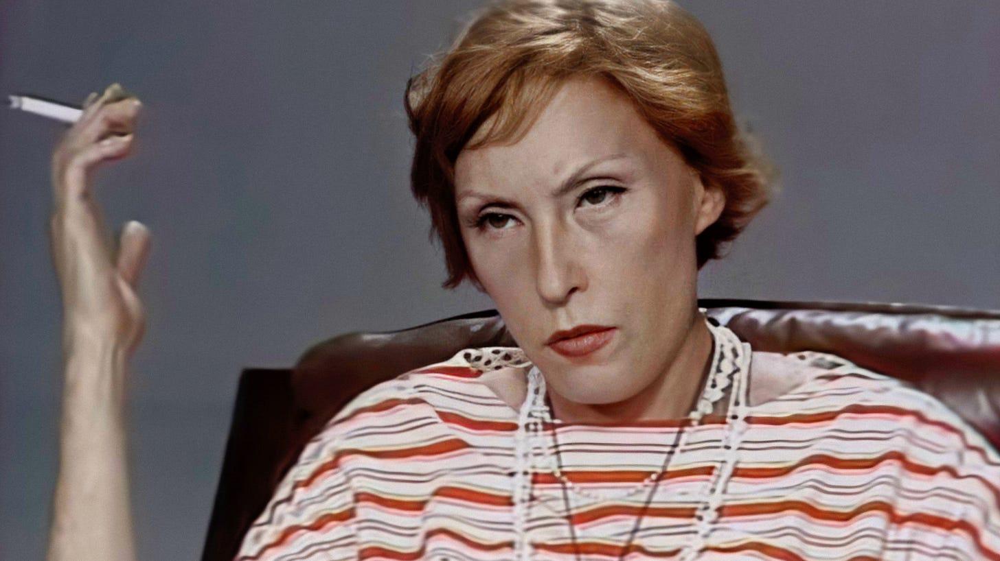 fotografia de Clarice Lispector na entrevista do programa Panorama, séria, olhando para o entrevistador, usando um vestido listrado, vários colares, segurando um cigarro com a mão direita na altura do rosto